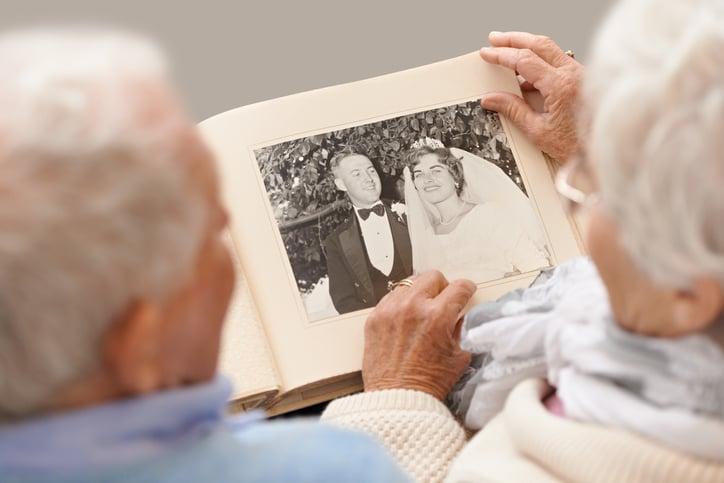 an older couple looking through a photo album