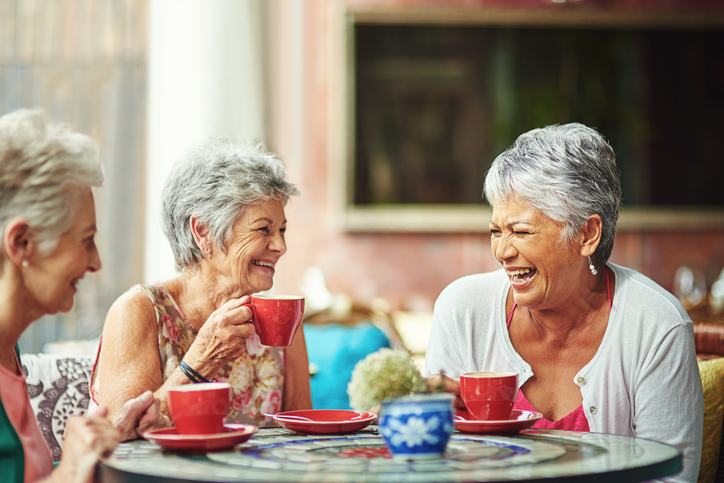 Three women enjoying some coffee while laughing together