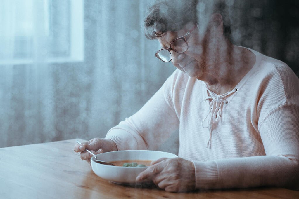 Lonely senior woman sitting at a table, dining alone thinking about socializing and nutrition.
