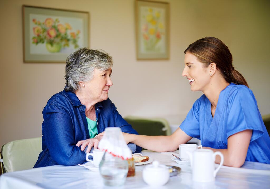 Caretaker speaking with senior mother over a healthy meal discussing why her appetite may have changed