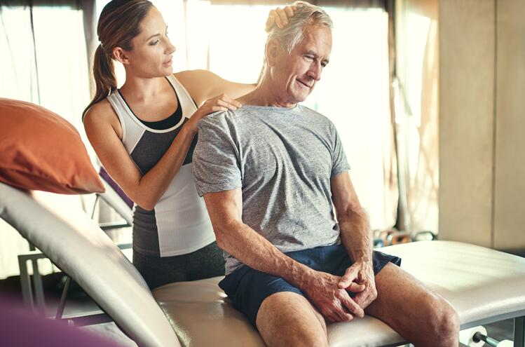 Senior man sitting on massage table with masseuse wondering what holistic health care is