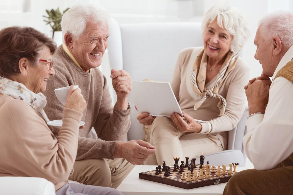 Group of seniors drinking coffee who are playing chess in an Assisted Living Facility