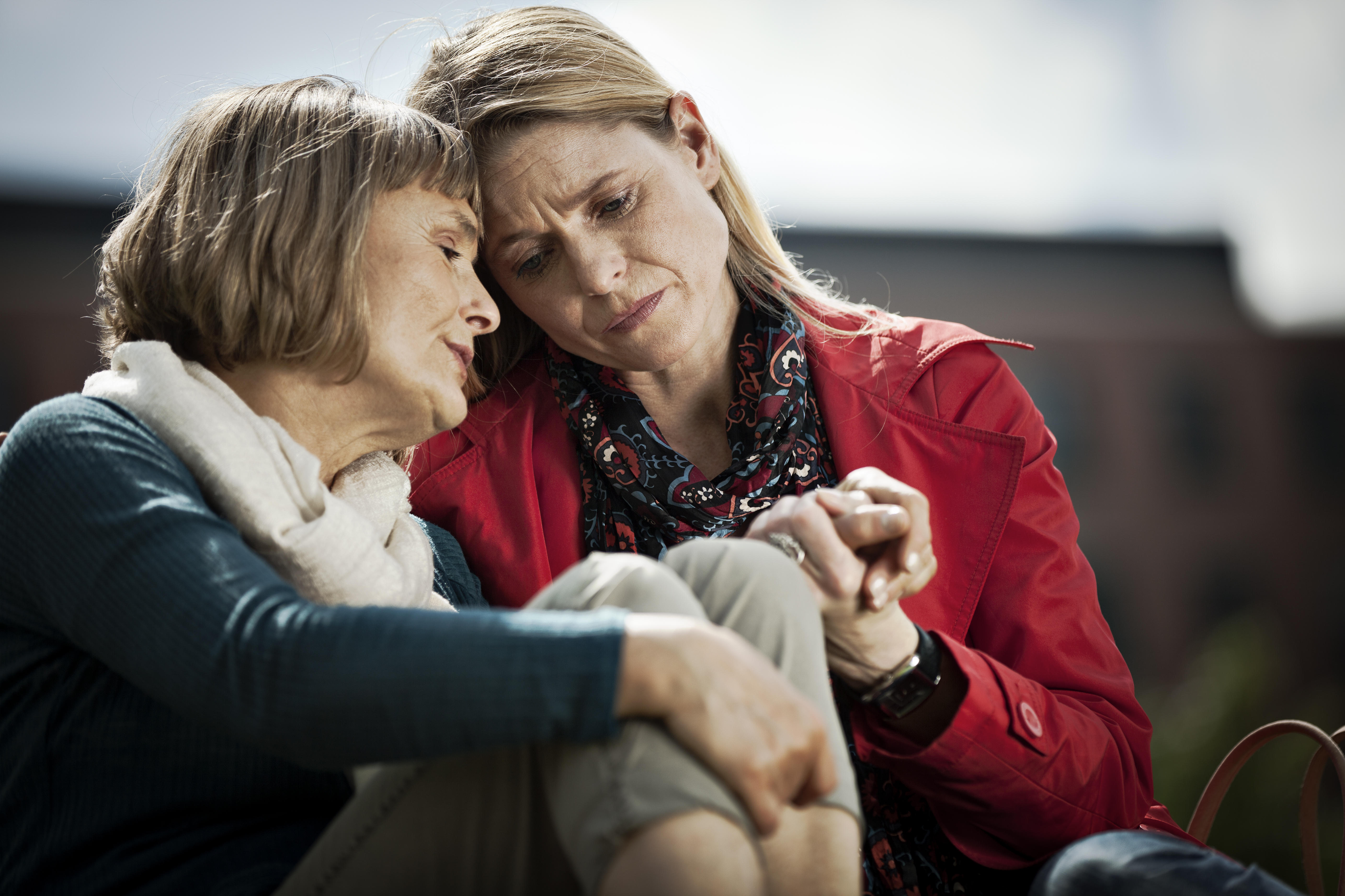 Mother and Daughter sharing an emotional moment on a bench outside