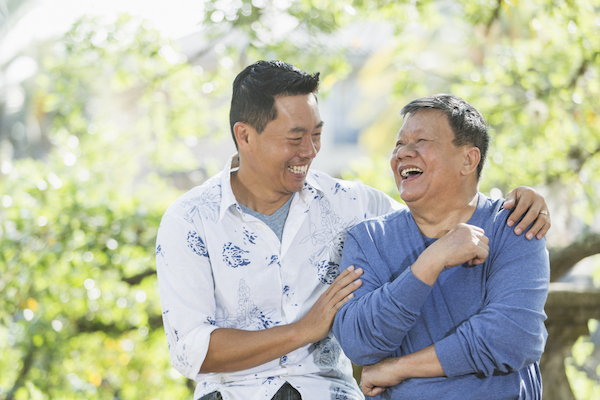 Adult son laughing with his elderly father