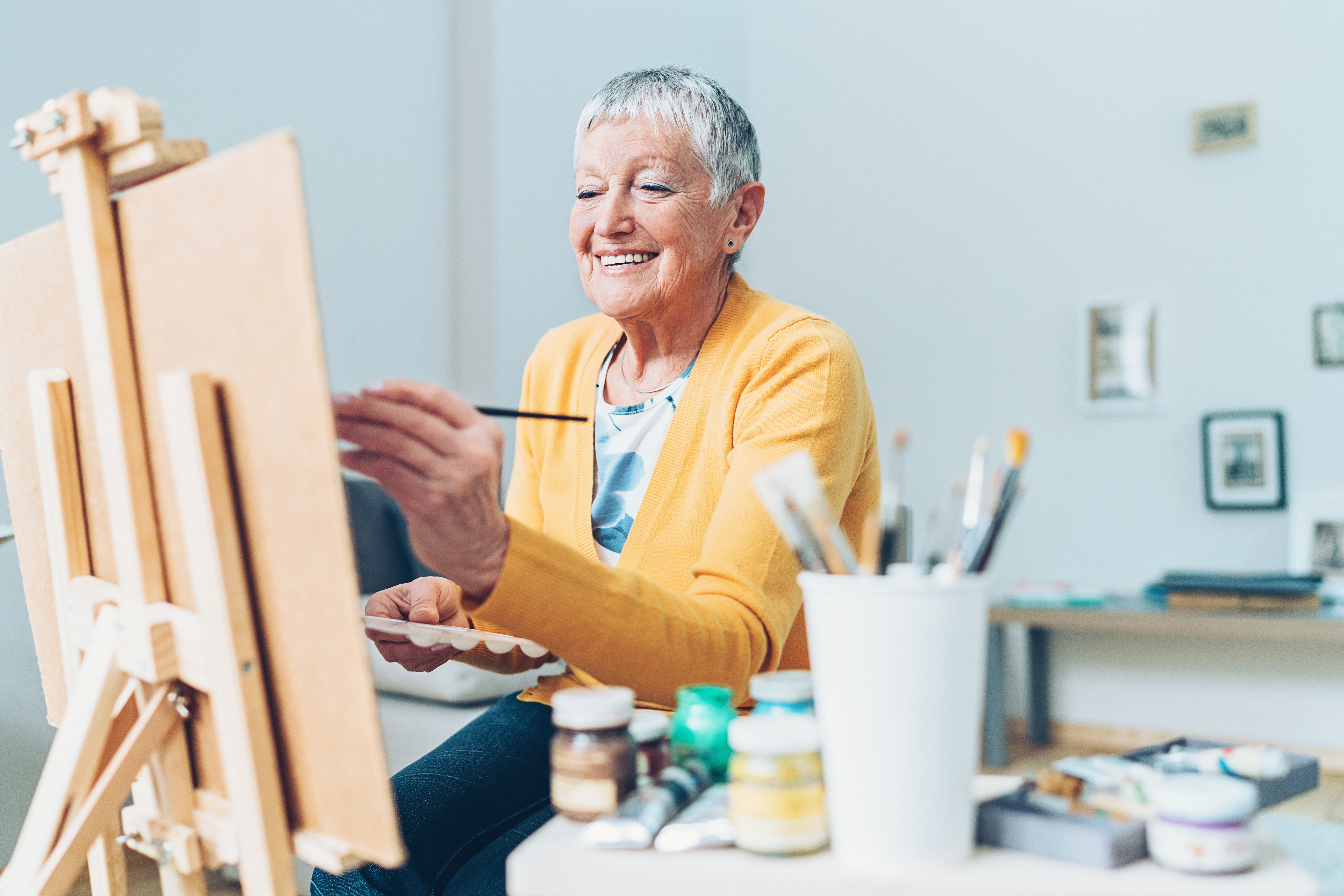 Senior with alzheimer's keeping active and engaged by painting in assisted living