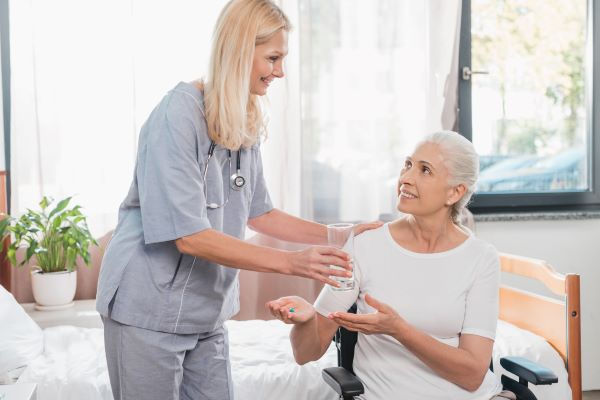 Healthcare professional giving an elderly woman her medication and water