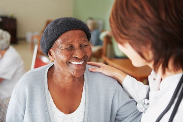 Assisted living resident smiling at a healthcare professional