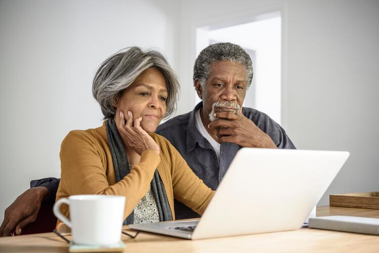 Senior couple looking at computer researching if assisted living costs are affordable