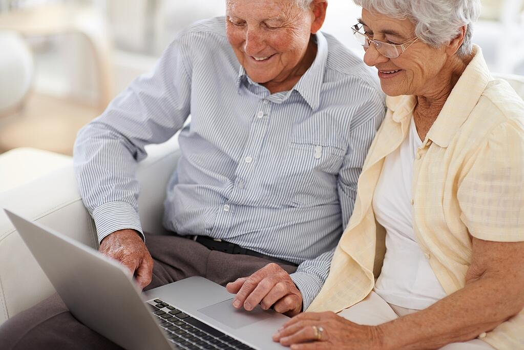 elderly couple on computer researching assisted living costs questions