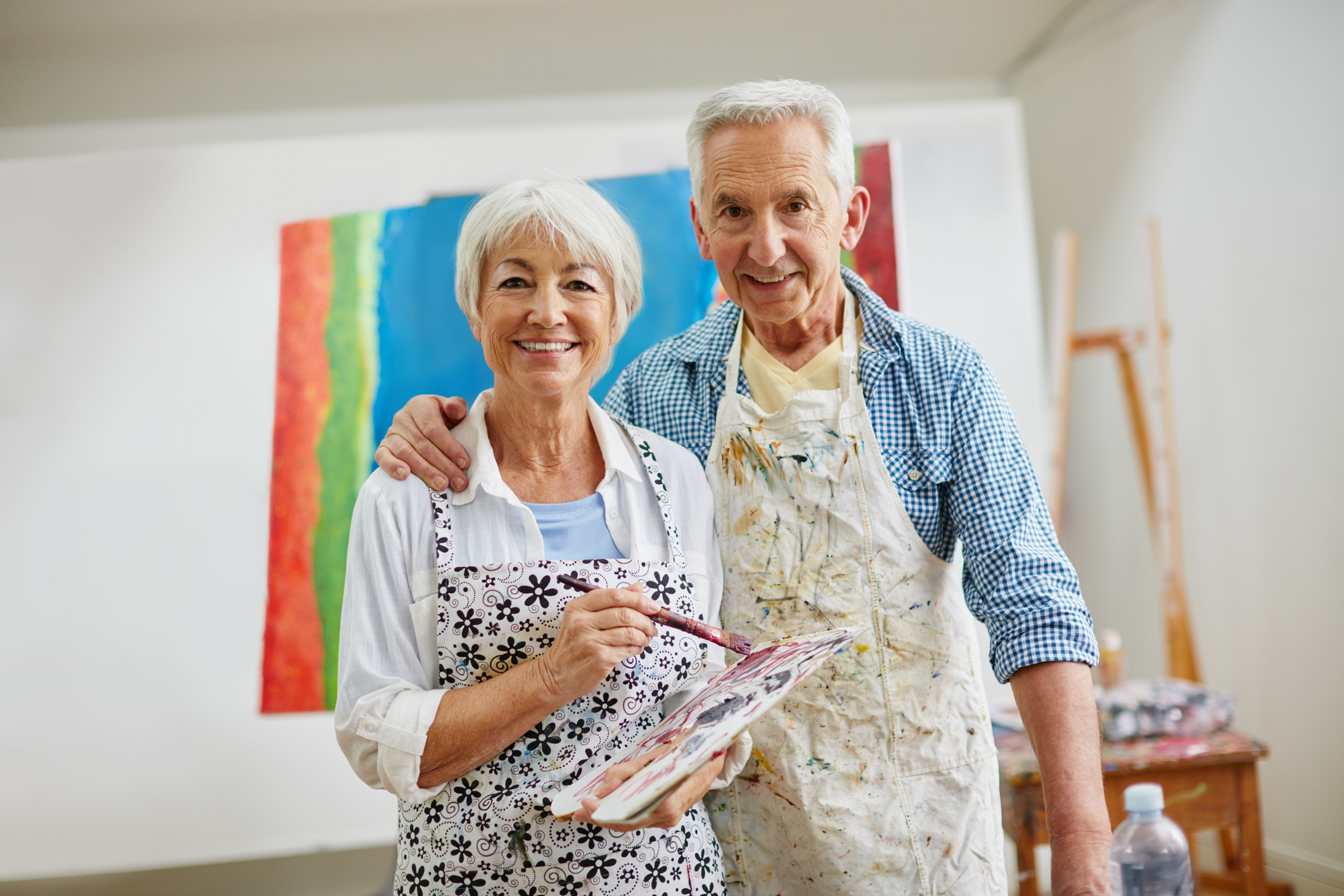 Husband and wife painting together and smiling for a photo