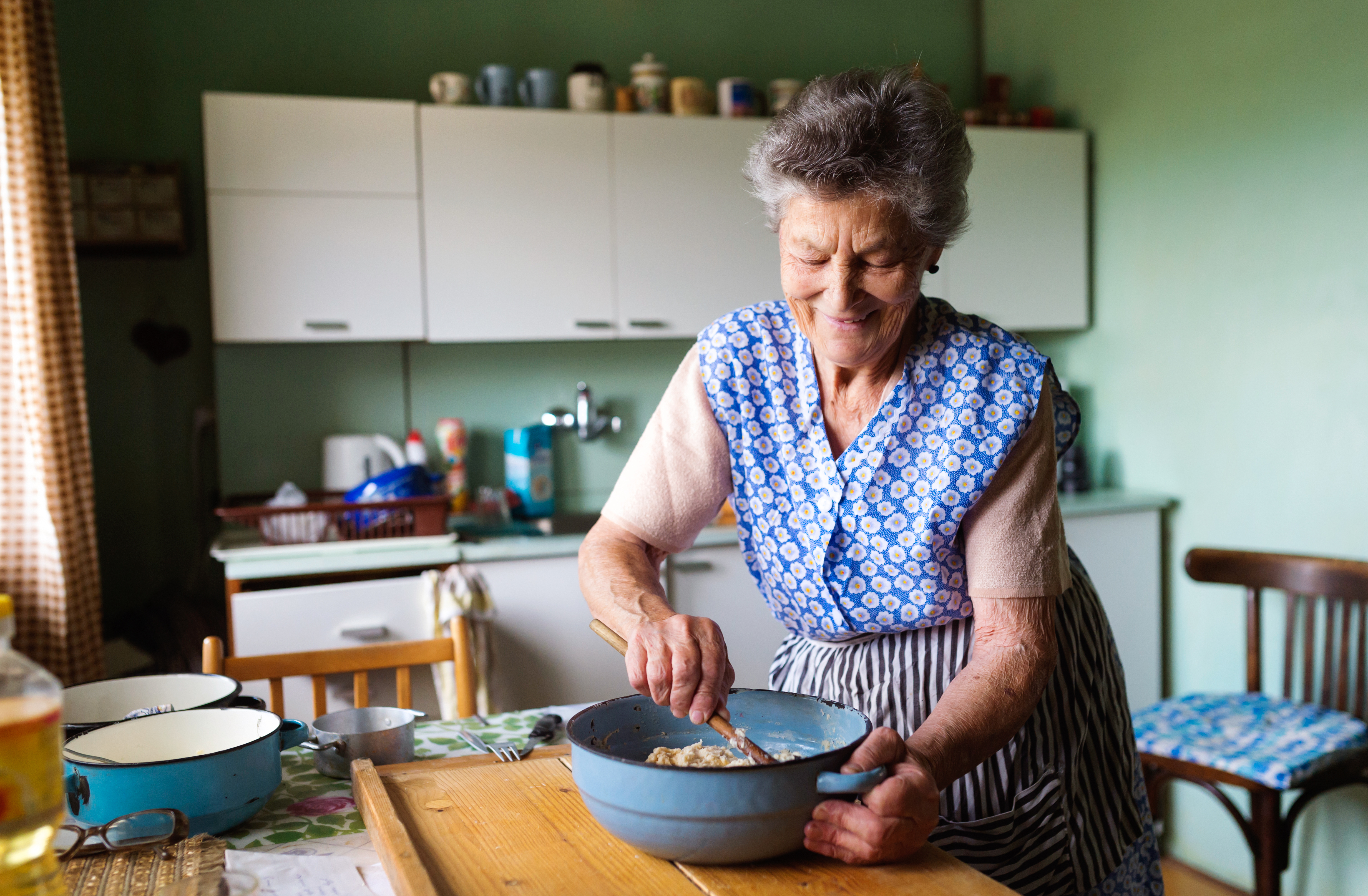 Elderly women baking in her kitchen with a smile on her face