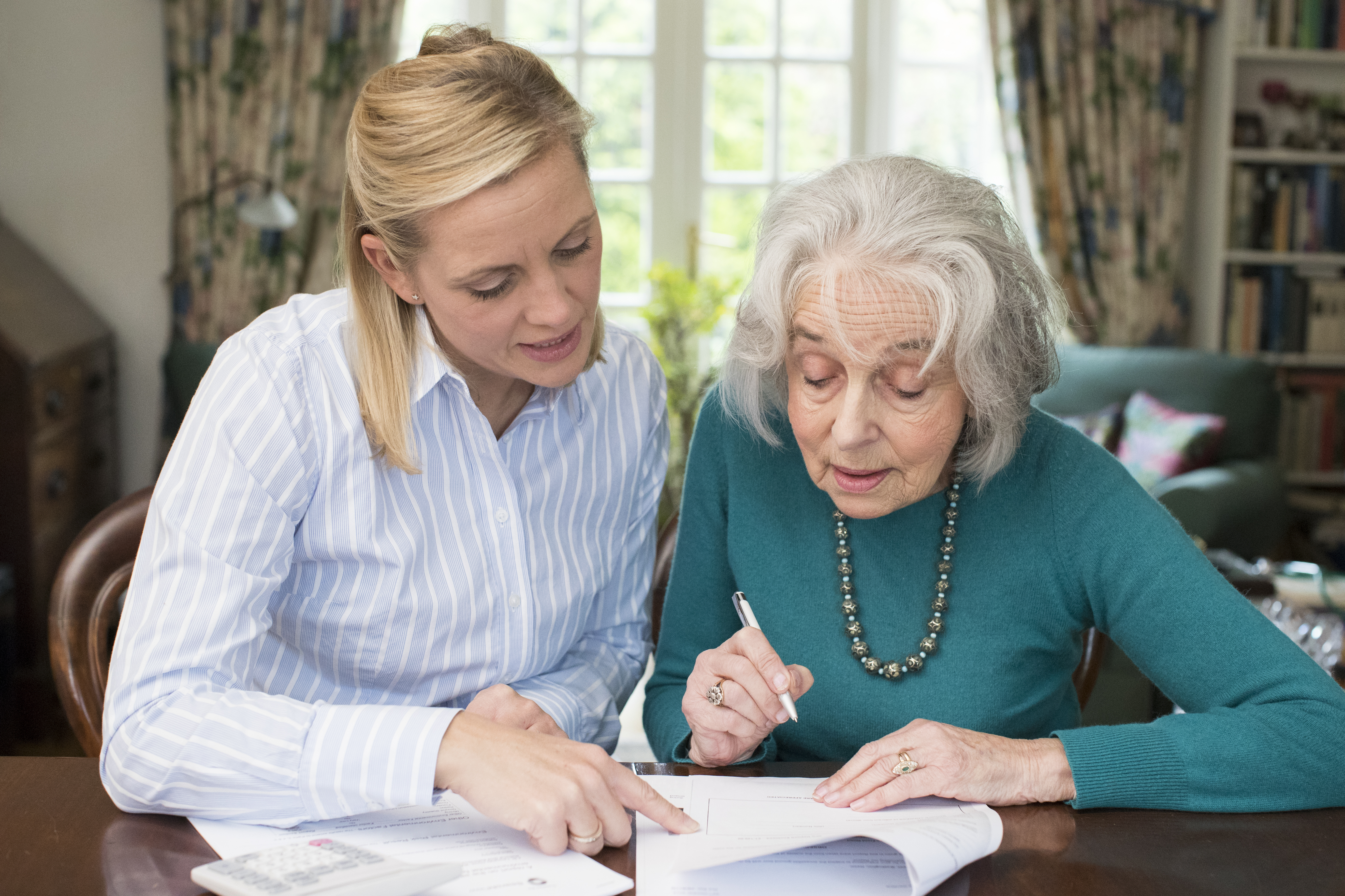 Mother and daughter going over paper documents for Power of Attorney